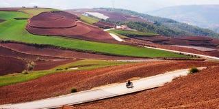 Bello paesaggio rurale in sud della Cina, terra rossa di Dongchuan Uomini cinesi locali che guidano motociclo sulla strada asfalt fotografie stock