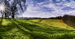 Bello panorama di Rolling Hills, di erba verde e di cielo blu Immagine Stock