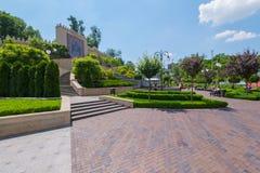 Bello parco per resto con i prati inglesi verdi succosi degli ampi banchi dei percorsi ed alta una parete decorata con gli orname Immagini Stock