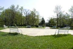 Bello parco verde con i banchi di legno bianchi Bello parco verde con una lunga strada Immagine Stock