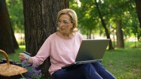Bello pensionato femminile che si siede nel parco con il computer portatile e che compera online stock footage