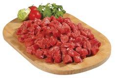 Bello pezzo della carne cubato rosso crudo fresco sul bordo di legno del taglio isolato sopra fondo bianco Immagini Stock