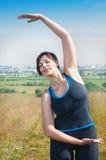 Bello più l'allungamento della donna di dimensione all'aperto Fotografia Stock Libera da Diritti