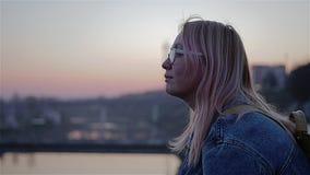 Bello piano di una ragazza che si siede sull'argine del fiume durante il tramonto Sulla lente bianca della ragazza archivi video