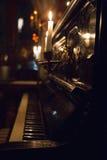 Bello piano nero con il coperchio aperto e una candela bruciante dentro Fotografia Stock