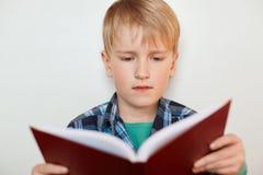 Bello piccolo allievo con capelli biondi che guardano seriamente nel libro che concentra espressione mentre preparandosi con il h Fotografie Stock