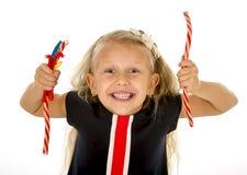 Bello piccolo bambino femminile con gli occhi azzurri che mangia la caramella della liquirizia della fragola Fotografia Stock Libera da Diritti