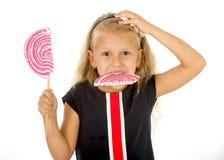Bello piccolo bambino femminile con gli occhi azzurri dolci ed i capelli biondi lunghi che mangia la caramella enorme di spirale  Immagini Stock