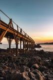 Bello pilastro di legno alla costa del mare con un bello tramonto nei precedenti immagini stock libere da diritti