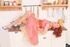 Bello pinup dai capelli rossi che sorride felicemente ragazza che posa in un retro vestito rosso nella cucina da solo fotografia stock