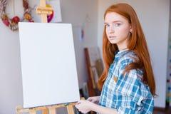 Bello pittore della donna che sta vicino al cavalletto in bianco nell'aula di arte Fotografie Stock