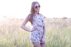 Bello prato di verde del campo della ragazza in vestito delicato dal parco di estate, godente dello svago, stile di modo, vita di Immagini Stock