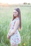 Bello prato di verde del campo della ragazza in vestito delicato dal parco di estate, godente dello svago, stile di modo, vita di Fotografia Stock