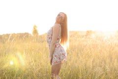 Bello prato di verde del campo della ragazza in vestito delicato dal parco di estate, godente dello svago, stile di modo, vita di Fotografie Stock Libere da Diritti