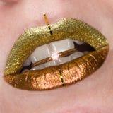 Bello primo piano con le labbra grassottelle femminili con trucco di colore dell'oro Cosmetico di scintillio Anello dorato con br fotografie stock libere da diritti