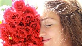 Bello primo piano della donna che sorride ed aroma di fiuto dei fiori delle rose rosse Vento nella ragazza dei capelli stock footage