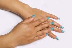 Bello primo piano delle mani di una giovane donna con il manicure blu lungo sulle unghie I fotografia stock