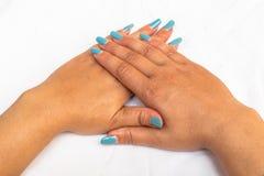 Bello primo piano delle mani di una giovane donna con il manicure blu lungo sulle unghie fotografia stock
