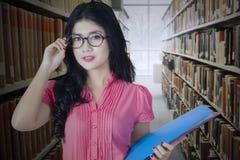 Bello principiante con i vetri in biblioteca Fotografia Stock