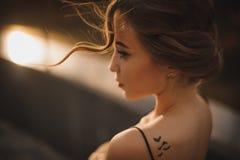 Bello profilo della ragazza con il tatuaggio sulla spalla, fuoco molle Fotografia Stock Libera da Diritti