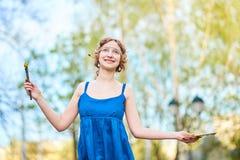 Bello ragazza-artista sulla via in un vestito blu, sorridente, con le nappe e la tavolozza in sue mani fotografie stock libere da diritti