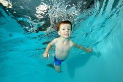 Bello ragazzino che nuota underwater nello stagno su fondo blu Ritratto Fucilazione sotto l'acqua al fondo Fotografia Stock