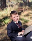Bello ragazzino che sorride mentre sedendosi con un computer portatile sulla natura Fotografie Stock Libere da Diritti