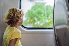 Bello ragazzo del bambino che guarda fuori la finestra del treno fuori, mentre  Immagini Stock
