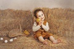 Bello ragazzo riccio-dai capelli che si siede accanto ad un orecchio dell'anatroccolo del fieno Immagine Stock