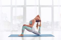 Bello rajakapotasana sportivo di posa di re Pigeon di asana di yoga di pratiche della donna degli Yogi di misura allo studio di y fotografie stock
