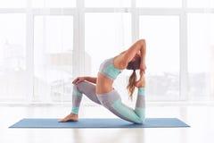 Bello rajakapotasana sportivo di posa di re Pigeon di asana di yoga di pratiche della donna degli Yogi di misura allo studio di y fotografia stock