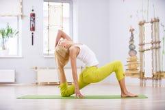 Bello rajakapotasana sportivo di posa di re Pigeon di asana di yoga di pratiche della donna degli Yogi di misura nella stanza di  Immagine Stock Libera da Diritti