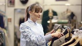 Bello ricerca adulto della donna vestiti nel negozio dell'abbigliamento ed esaminare pullover grazioso ma prenderlo di nuovo ad a stock footage