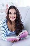 Bello rilassamento castana sorridente sullo strato e leggere un libro Fotografia Stock