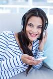Bello rilassamento castana sorridente sullo strato e sulla musica d'ascolto Fotografia Stock