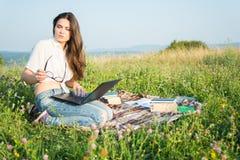 Bello rilassamento femminile con i libri ed il computer portatile fuori Immagini Stock Libere da Diritti
