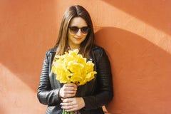 Bello ritratto della donna castana che tiene i fiori gialli della molla nel giorno soleggiato fotografia stock