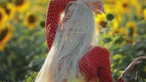Bello ritratto della donna nel giacimento del girasole, movimento lento stock footage