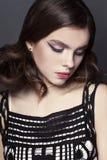 Bello ritratto della ragazza con l'acconciatura piacevole in vestito da sera su fondo nero Fotografia Stock