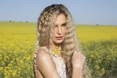Bello ritratto di una ragazza della campagna che posa sopra il campo giallo Immagini Stock