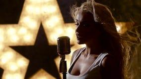 Bello rocksinger femminile con il retro microfono video d archivio