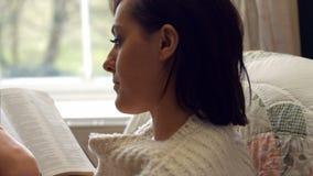 Bello romanzo della lettura della donna in camera da letto stock footage