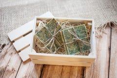 Bello, sapone fatto a mano fragrante nella condizione della scatola di legno su un fondo della tela da imballaggio e di legno fotografie stock