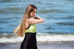 Bello scaldarsi femminile sulla spiaggia Atleta che pareggia durante l'allenamento all'aperto, affrontante oceano Immagine Stock Libera da Diritti