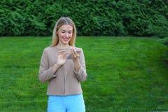 Bello schermo di sguardo femminile dello smartphone e sorrisi, supporti Fotografie Stock Libere da Diritti