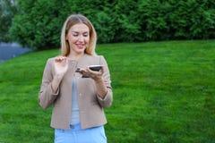 Bello schermo di sguardo femminile dello smartphone e sorrisi, supporti Fotografia Stock Libera da Diritti