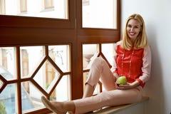 Bello sedile biondo della donna vicino alla mela di verde di sorriso della finestra Fotografia Stock Libera da Diritti