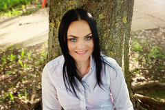 Bello sedile della giovane donna sotto l'albero Fotografia Stock