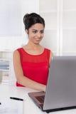 Bello segretario asiatico nel lavoro rosso con il computer portatile all'ufficio. Fotografia Stock Libera da Diritti