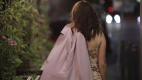 Bello sguardo della donna indietro alla macchina fotografica ed andare via nella città di notte, movimento lento stock footage